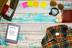 Travel preparations in full swing concept. Preparing for vacations activities top view concept - travel bag with passport, money and road map, checkered shirt Royalty Free Stock Photography