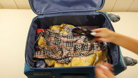 Travel preparations on wooden table. Woman putting clothes in suitcase. 1920x1080 stock footage