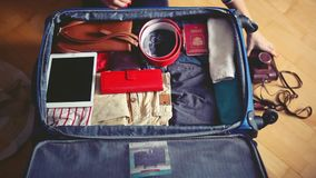 Travel preparations on wooden table. Woman putting clothes in suitcase. 1920x1080 stock video