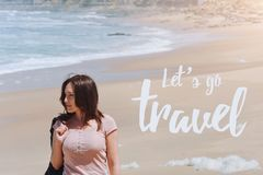 Travel quote, words Let`s Go Travel. Summer vacation happiness carefree joyful woman standing on sand enjoying tropical. Beach. Lonely traveler on the ocean Stock Photos