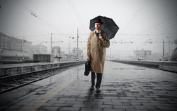 Travel in the rain. Businessman with umbrella standing on a train platform Royalty Free Stock Photos