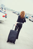 Travel: Rear View Of Woman Walking Through Parking Lot Stock Photo