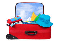 Travel red suitcase packed for vacation. Travel red suitcase. Packed for vacation in sea resort. Personal belongings: hat, cream, towel. Isolated on white Stock Image