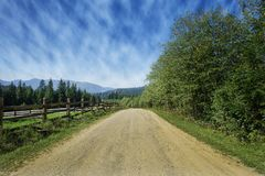 Travel road on the farm with green grass and blue sky with clouds on the farm in beautiful summer sunny day. Clean, idyllic, land stock photo