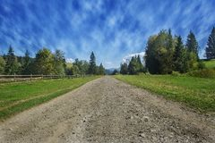 Travel road on the farm with green grass and blue sky with clouds on the farm in beautiful summer sunny day. Clean, idyllic, land royalty free stock photos