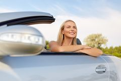 Happy young woman in convertible car stock images