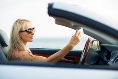 Woman in convertible car taking selfie Royalty Free Stock Photos