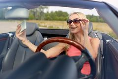 Woman in convertible car taking selfie Stock Images