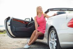 Happy young woman porisng in convertible car Stock Images