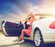 Woman in convertible car over evening sky Stock Image