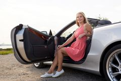 Happy young woman posing in convertible car royalty free stock image