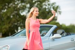 Woman posing at convertible car and taking selfie Stock Photography