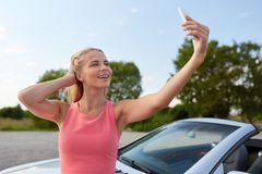 Woman posing at convertible car and taking selfie Royalty Free Stock Image