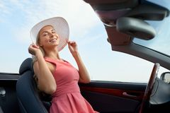 Happy young woman in convertible car royalty free stock image