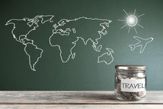 Travel savings jar. By a chalkboard with a world map Stock Images