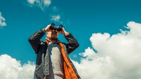 Travel Search Scout Concept. Hiking Man Looking Through Binoculars In The Distance Against The Sky. Low Angle Point Shoot royalty free stock photography