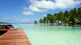 Boat at pier on tropical beach in french polynesia. Travel, seascape and nature concept - boat moored at wooden pier on tropical beach in french polynesia stock video footage