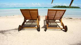 Two sunbeds on tropical beach in french polynesia. Travel, seascape and nature concept - two wooden sunbeds on tropical beach in french polynesia stock footage