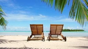 Two sunbeds on tropical beach in french polynesia. Travel, seascape and nature concept - two wooden sunbeds on tropical beach in french polynesia stock video