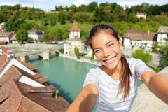 Travel selfie by woman in Bern Switzerland. Happy smiling multiracial Asian Caucasian girl taking self portrait photograph sitting on Nydeggbrucke by Aare Royalty Free Stock Photo