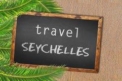 Travel Seychelles palm trees and blackboard on sandy beach Stock Photos