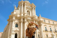 Travel in Sicily. Back view of beautiful girl visiting Syracuse Cathedral on sunny day. Summer holidays in Italy.  royalty free stock photo