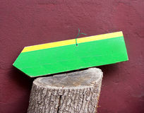 Travel Sign on Bole with Burgundy Wall. Wooden Yellow and Green Travel Sign on Bole with Burgundy Wall Behind Stock Photos