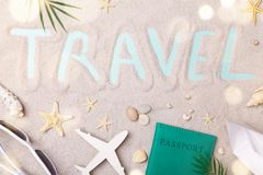 Travel sign on sand background with summer holidays, trip and vacation accessories. Flat lay style. Travel sign on sand background with summer holidays, trip and royalty free stock image