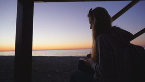 Travel: Silhouette of beautiful girl tourist. Drawing sunset at the beach. Medium shot, slow motion 60fps, handheld, HD stock video footage