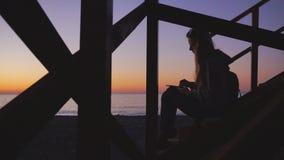 Travel: Silhouette of beautiful girl tourist. Drawing sunset at the beach. Medium shot, static, HD stock video