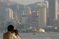 Travel Snap. Asian tourist photographing the Hong Kong skyline from the Kowloon side Royalty Free Stock Photography