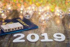 Travel 2019 still life concept with passport and fun lights on wooden board, shallow DOF. Travel still life concept with passport and fun lights on wooden board stock photos