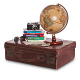 Travel still life. Still-life photo of an old brown leather suitcase with camera, travel guides, world globe, sunglasses, stamped passport and money. Isolated on Royalty Free Stock Photos