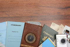 Travel Still Life on Wood Table. High angle shot of a travel still life. Items include: passport, wallet, post cards, camera, pictures, maps, and itinerary Stock Image