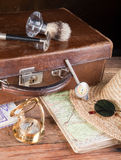 Travel stuff. Vintage suitcase, maps, compass and old distance meter Stock Photos