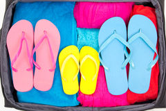 Travel suitcase with clothing and flip-flops. Full travel suitcase with clothing and flip-flops Royalty Free Stock Photos