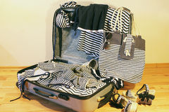Travel suitcase. Suitcase with striped clothes and accessories in a marine style Royalty Free Stock Photography