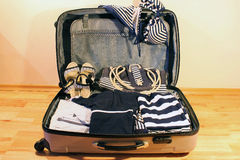 Travel suitcase. Suitcase with striped clothes and accessories in a marine style Stock Image