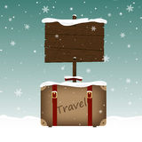 Travel suitcase and a wooden signboard in snow. Christmas and New Year theme. Place for your text Royalty Free Stock Image