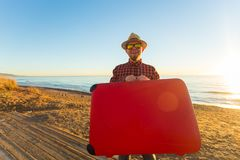 Travel and summer concept - Male tourist carrying a red suitcase at the beach.  royalty free stock image