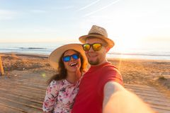 Travel, summer and holiday concept - Lovely couple taking selfie on a beach.  stock photo