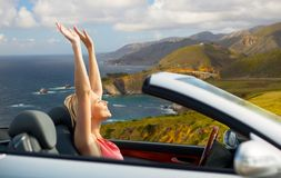 Happy woman in convertible car on big sur coast. Travel, summer holidays, road trip and people concept - happy young woman in convertible car enjoying sun over royalty free stock image
