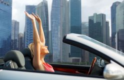 Woman in convertible car over singapore city. Travel, summer holidays, road trip and people concept - happy young woman in convertible car enjoying sun over stock image