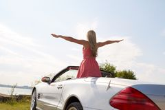 Happy young woman in convertible car at seaside Stock Photography