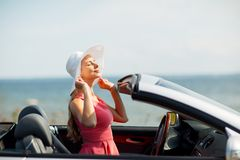 Happy young woman in convertible car. Travel, summer holidays, road trip and people concept - happy young woman wearing hat in convertible car enjoying sun royalty free stock photography