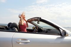 Happy young woman in convertible car. Travel, summer holidays, road trip and people concept - happy young woman wearing hat in convertible car enjoying sun stock photo