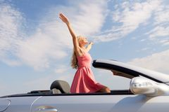 Happy young woman in convertible car stock photography