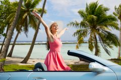 Happy young woman in convertible car over beach. Travel, summer holidays, road trip and people concept - happy young woman wearing hat in convertible car stock image
