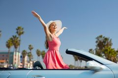 Happy young woman in convertible car. Travel, summer holidays, road trip and people concept - happy young woman wearing hat in convertible car enjoying sun over stock photo