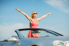 Happy young woman in convertible car. Travel, summer holidays, road trip and people concept - happy young woman wearing sunglasses in convertible car enjoying stock image